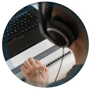 Man at computer using braille keyboard