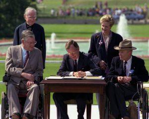 President Bush signing the ADA, requiring ADA compliance