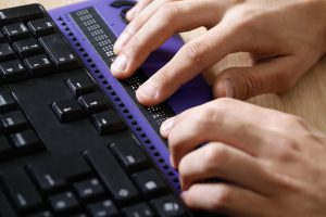 Hands typing on a Braille display. Equidox Accessibility Mission