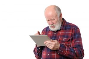 Senior bald man squinting at a tablet