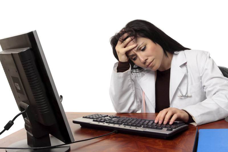 Doctor at a computer looking frustrated