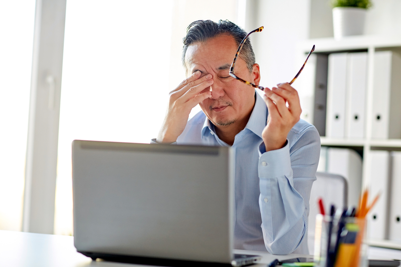 man at computer rubbing his eyes while holding glasses