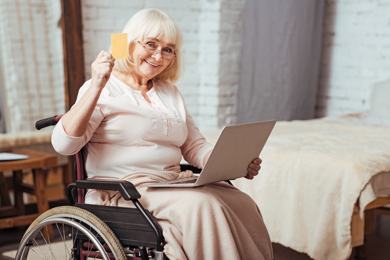 Older woman in wheelchair with laptop, cheerfully waving her credit card.