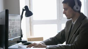 Man wearing headphones working at a computer. Professional testing was a digital accessibility lawsuit target.