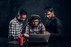 Three dark-skinned guys are chatting by a laptop wearing headphones