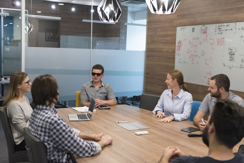 Man in sunglasses with a tablet at a conference table with a group of people
