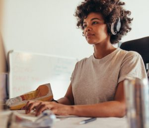 Woman wearing headphones using a computer, using a website with digital accessibility.
