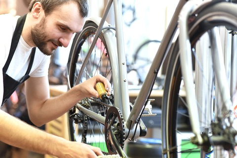 Man working at a bicycle shop facing third quarter accessibility lawsuits