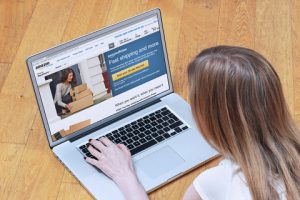 Woman using a laptop to shop online, facing digital accessibility issues which will result in ADA lawsuits.