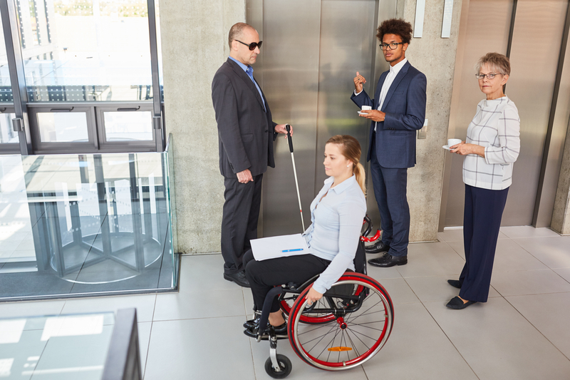 Diverse coworkers waiting for an elevator, working for one of many inclusive employers.